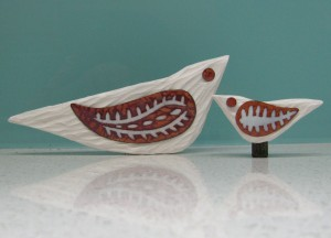 Carved wooden birds, painted and embellished with enamel on copper wings and eyes